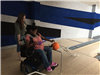 A young woman in a wheelchair rolling a bowling ball down a ramp