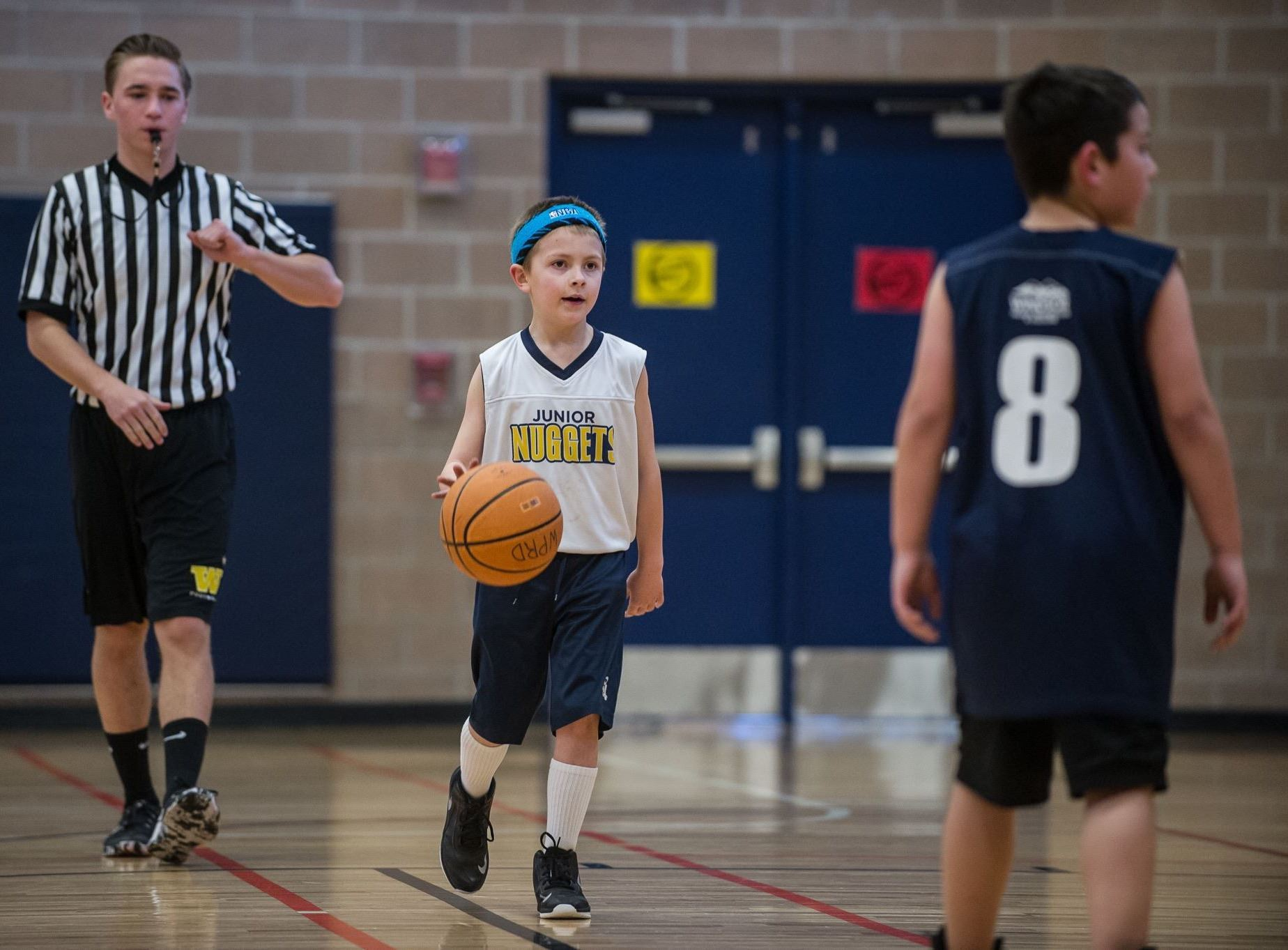 Boy Dribbling Basketball Followed by Referee