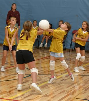 Two Girls Reach to Bump Volleyball