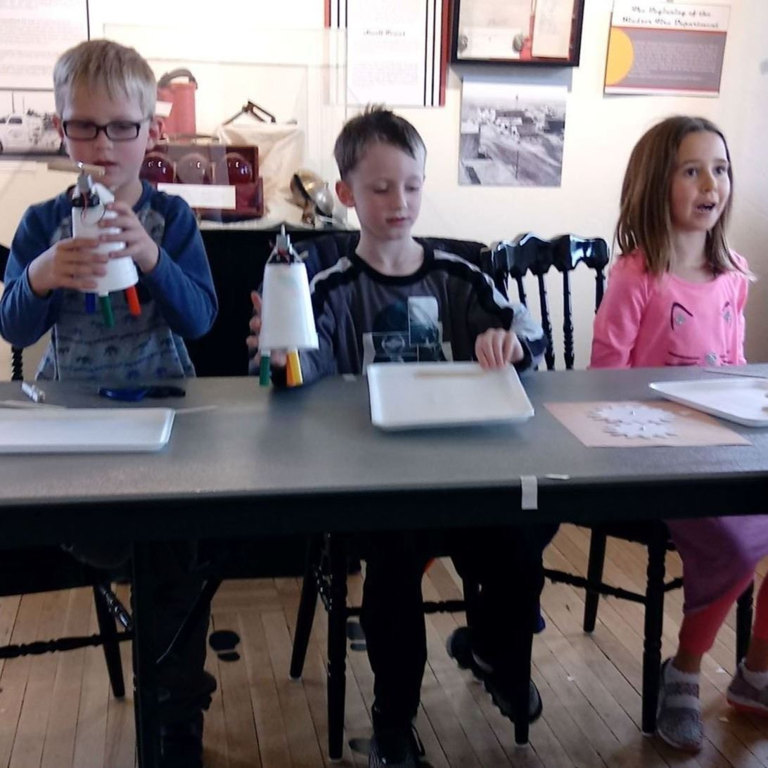 Three young children sitting at a table looking very excited to learn something new.