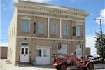 A two-story municipal building with an old vehicle out front